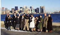 A recent tour group poses for a photo with Manhattan's skyline in the background.